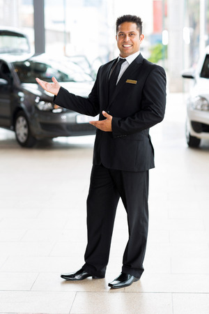 cheerful indian car salesman doing welcoming gesture photo