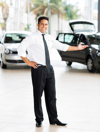 good looking indian car salesman standing at showroom presenting new cars photo