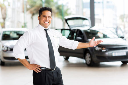 car dealer presenting new vehicle in showroom photo
