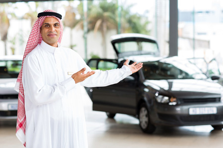 friendly arabian car salesman doing welcoming gesture photo