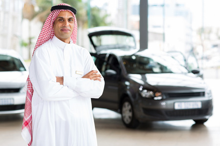 middle eastern male car dealer principal inside showroom photo