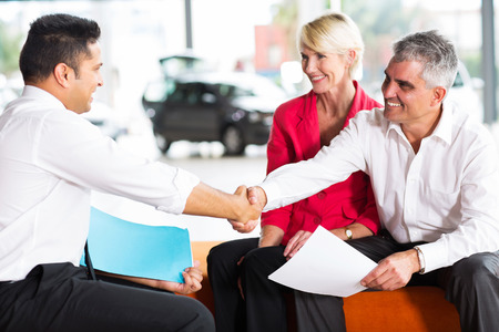 happy car salesman handshaking with senior buyer Stock Photo