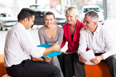 indian car dealer explaining sales contract to the family buying a car photo