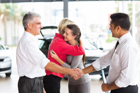 senior man buying car for his daughter handshaking with dealer after the sale photo