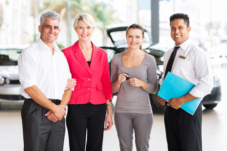 family of three standing with salesman at vehicle dealership after buying a new car photo