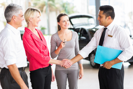 cheerful senior woman handshaking with car sales consultant at dealership photo