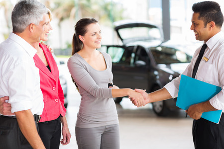vehicle salesman handshaking with young adult customer after the sale photo