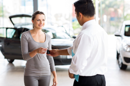 young woman receiving her new car key from salesman photo