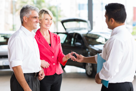 salesmen: senior couple receiving car key after buying a new car