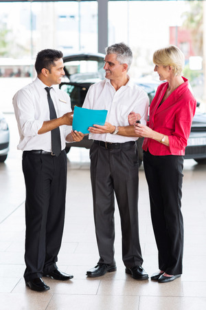 mid age couple buying a new car at dealership photo