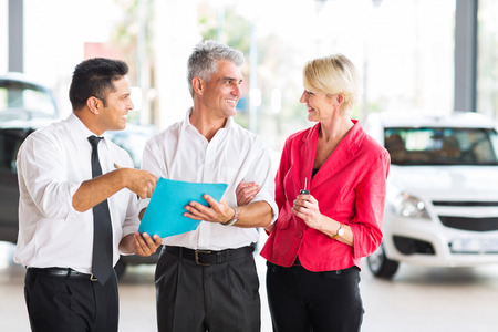 middle aged man talking to wife before buying a new car at dealership photo