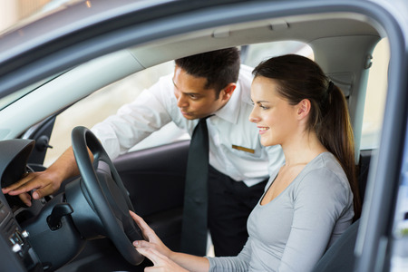 friendly salesman explaining car features to young female customer photo