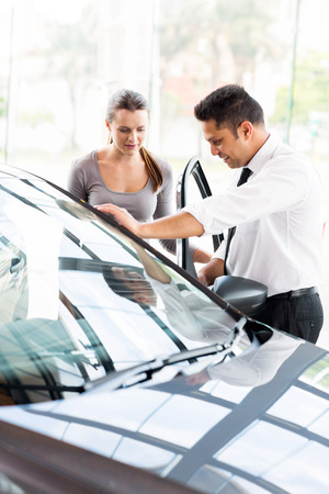 car sales consultant showing a new car to a potential buyer in showroom photo