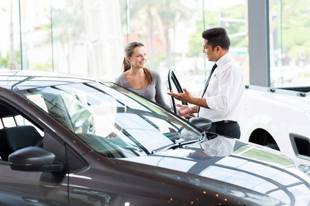 friendly vehicle dealer showing young woman new car photo