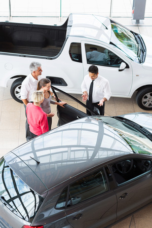 overhead view of car dealer showing new car to customers photo