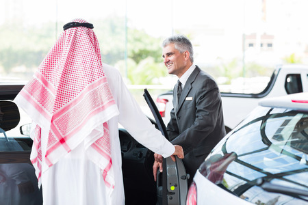 senior car salesman showing a new car to Arabian man photo