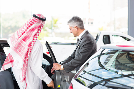 Arabian man getting in a new car for test drive at vehicle dealership photo