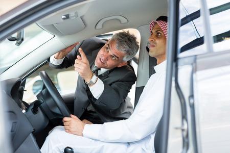 mature vehicle dealer showing Arabian customer car features photo