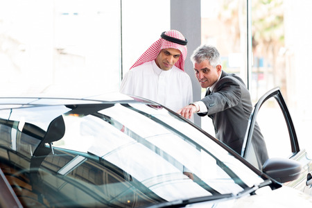 senior dealer pointing car features to potential Arabian buyer photo