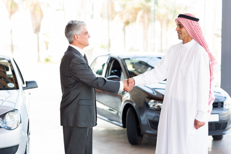 smiling middle aged car dealer handshake with arabian man photo