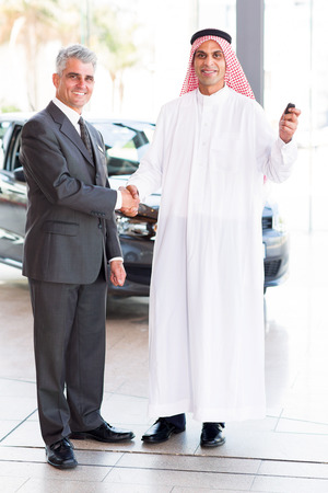 happy senior car salesman handshake with Arabic customer  photo