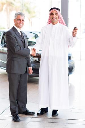 happy senior car salesman handshake with Arabic customer  photo