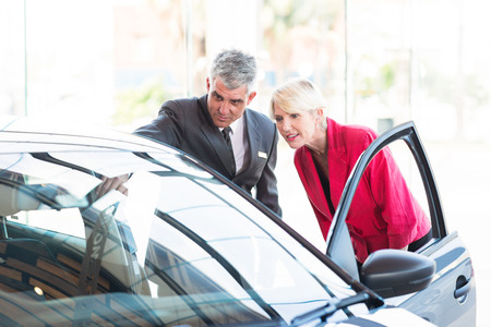 new age: mid age salesman showing new car to potential customer