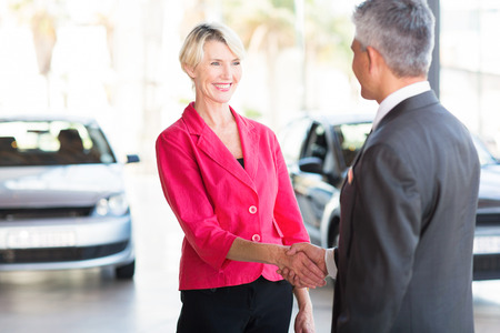 beautiful middle aged woman handshaking with car dealer photo