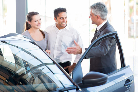 car showroom: mature salesman showing new car to a couple in showroom