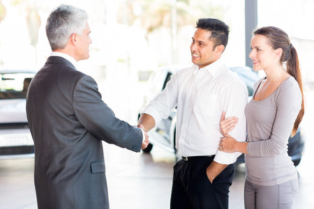 middle aged salesman handshaking with happy young couple photo