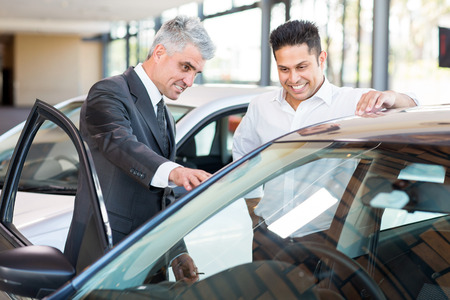 senior car salesman showing a new car to customer photo