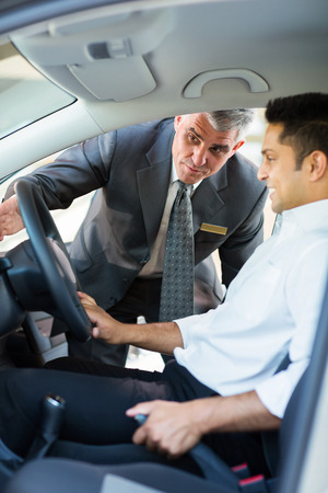 middle aged salesman showing new car interior to customer sitting inside the car photo