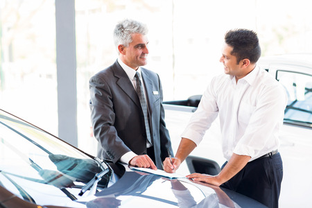 senior car salesman just made a sale to young customer Stock Photo