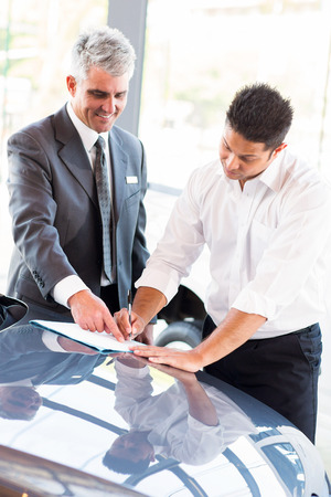 young man signing documents at car dealership with salesman photo