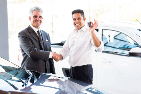 happy indian man showing new car key while handshaking with salesman photo