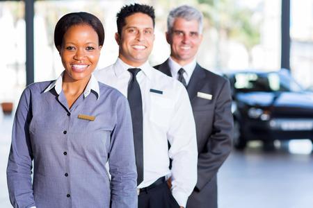showroom: multiracial vehicle sales team inside car showroom Stock Photo