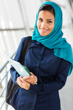muslim: beautiful middle eastern college girl holding books Stock Photo