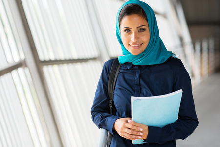 modern female middle eastern college student holding a book photo