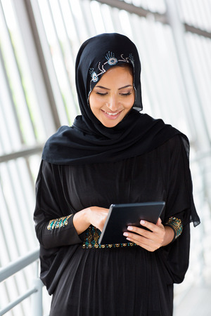 middle eastern clothes: happy middle eastern woman using tablet computer Stock Photo