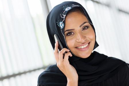 cheerful modern muslim woman talking on cell phone photo