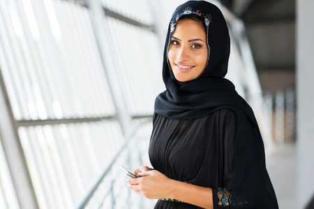 headscarf: pretty young arabian woman holding smart phone