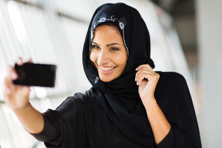 happy arabian woman taking self portrait using cell phone photo