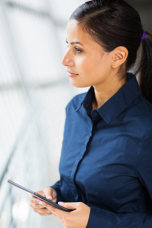 thoughtful businesswoman holding tablet computer photo