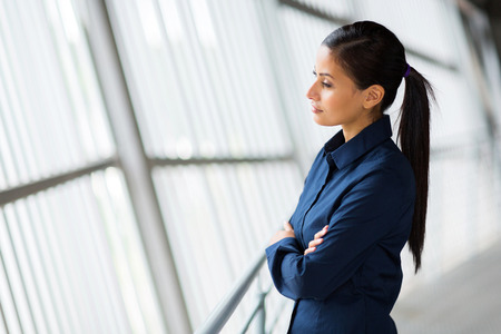 woman serious: thoughtful young entrepreneur looking outside the window