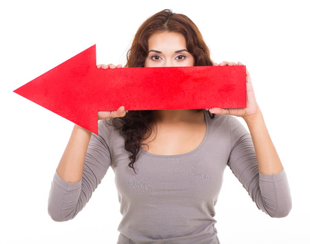 young girl holding red arrow sign pointing left