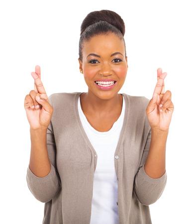 mooie Afrikaanse vrouw met vingers gekruist op wit wordt geïsoleerd Stockfoto