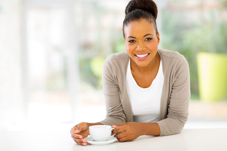 cute afro american woman drinking coffee at home photo