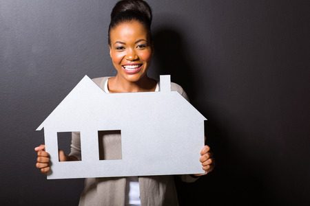 property agent: gorgeous african woman holding home symbol isolated on black background Stock Photo