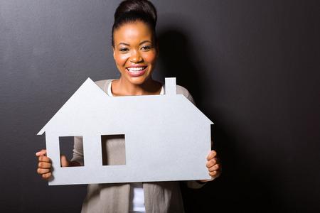 prachtige Afrikaanse vrouw holding huis symbool geïsoleerd op een zwarte achtergrond