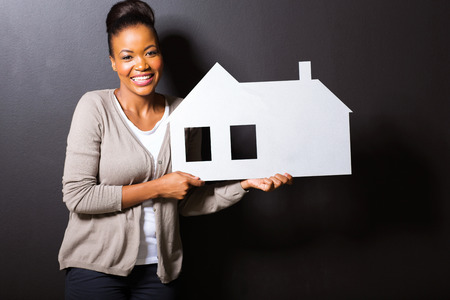 sales agent: beautiful young woman holding white paper house